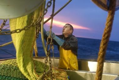 Marin pêcheur déroulant une partie du chalut en vue de sa réparation, sur fond de lever de soleil.